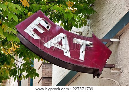Very Old Outdoor Neon Sign In The Daylight Shaped Like An Arrow Spelling Eat