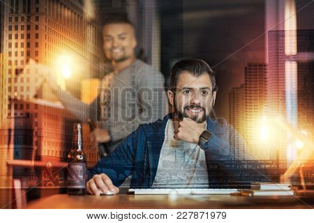 Cozy Evening. Young Bearded Man Sitting In Front Of A Laptop And Smiling While His Close Friend Stan