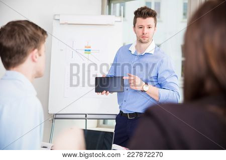 Confident Businessman Showing Tablet Computer To Colleagues In Office