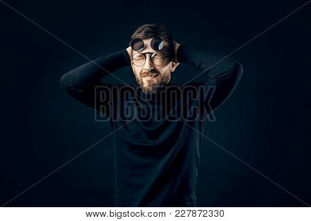 Surprised Bearded Man In Black Rounded Glasses Holding His Head With Both Hands Isolated On Dark Bac