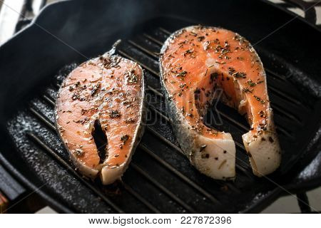 Two Raw Salmon Steaks With Spices And Herbs On A Grill Pan. Close Up Bbq Grilled Salmon Steaks On Bl