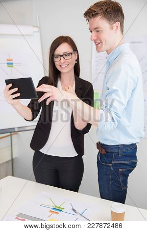 Young Businessman And Male Colleague Using Digital Tablet At Desk In Office