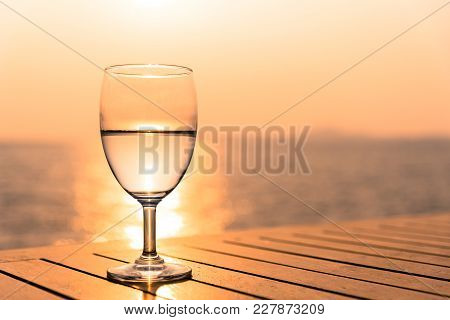 Silhouette Glass Of Wine On A Wooden Table With  Seascape And Skyline In The Evening With Sunset Ton