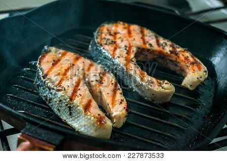 Two Two Toasted Salmon Steaks With Spices And Herbs On A Grill Pan. Close Up Bbq Grilled Salmon Stea