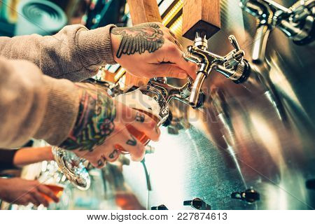 Hand Of Bartender Pouring A Large Lager Beer In Tap. Soft, Vintage Instagram Effect On Photo. Pourin