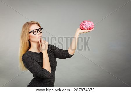 Woman Thinking And Holding Fake Brain