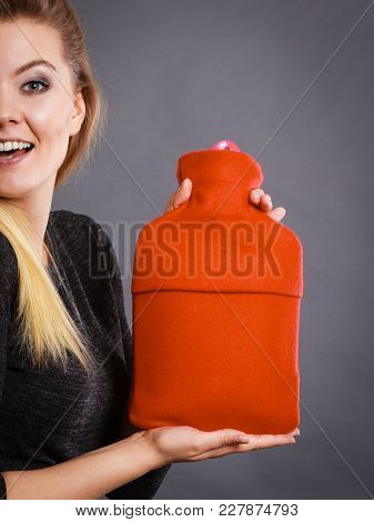 Positive Smiling Woman Recommending Warm Hot Water Bottle In Red Soft Fleece Cover, On Grey. Health