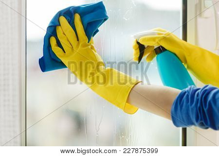 Female Hand In Yellow Gloves Cleaning Window With Blue Rag And Spray Detergent. Spring Cleanup, Hous