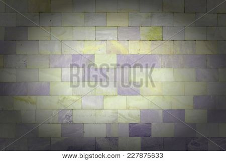 The Wall Is Made Of Marble Yellow And Violet Tiles. Beautiful Stone Texture. Empty Unusual Backgroun
