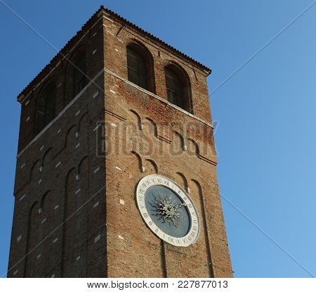 High Clock Tower In Downtown Of Chioggia Island Near Venice In Italy
