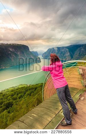 Tourist Woman On Stegastein Viewpoint Enjoying Aurland Fjord View In Evening Time, Sogn Og Fjordane,