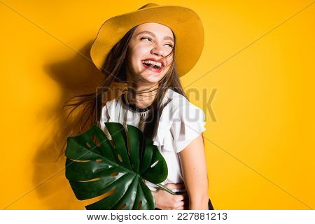 Happy Laughing Girl Model In A Fashionable Hat Holds A Green Leaf, On A Yellow Background