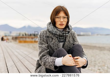 Stylish Dark-haired Girl In A Gray Coat And Glasses Walks, Enjoying Cloudy Weather