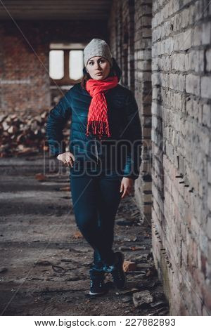Photo Of A Young Beautiful Girl In Ruins Against A Background Of Brick Walls In A Jacket And Trouser
