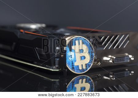 Cryptocurrency Mining Concept With Blue Bitcoin On A Videocard On Black Background.