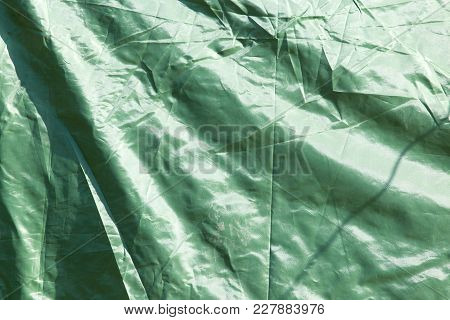 Green Crumpled Fabric As Background . Photo Of An Abstract Texture