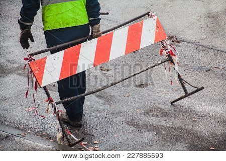 Construction Site Worker Holding Red And White Striped Limiter In His Hand Standing On Asphalt Surfa