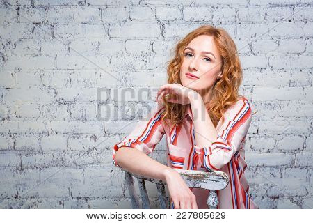 Portrait Beautiful Young Woman Student With Red Curly Hair And Freckles On Her Face Sitting On A Woo
