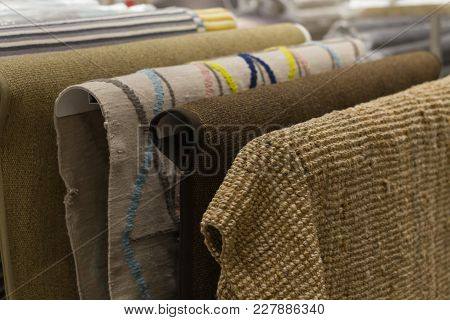 New Carpets Hang In The Mall. Selection Of Carpets From The Assortment With Different Texture And Co