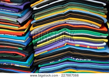 Close Up Of A Stack Of An Assortment Of Colorful Folded T-shirts.
