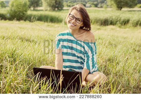 Smiling Womanl Sitting On The Grass In Bright Summer Day And Working On The Computer. Using Laptop O