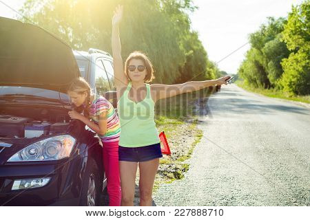 Woman Driver With A Child On A Country Road, Near A Broken Car. She Needs Help