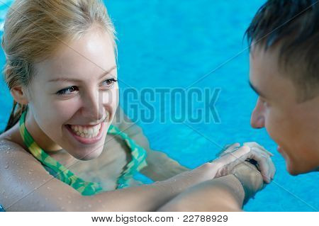 Young girl flirting with a boy at the swimming pool