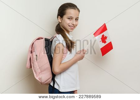 Schoolgirl 10 Years In White T-shirt With A Backpack Holding The Flag Of Canada, Background Bright W