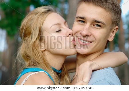 Teenage boy kissed by his girlfriend