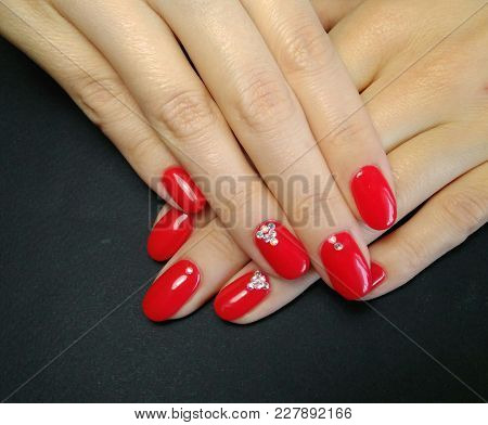 Elegant Manicure. Red Gel Nail Polish With Rhinestones On A Black Background.