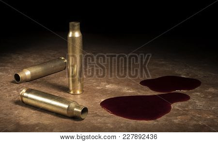 Three Empty Ar-15 Casings With Blood On A Brown Floor