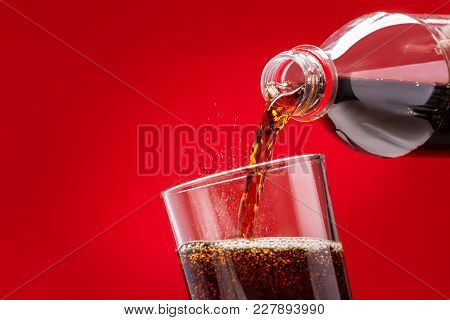 Pouring Refreshing Sugary Soft Drink From A Plastic Bottle Into A Glass On A Red Background poster