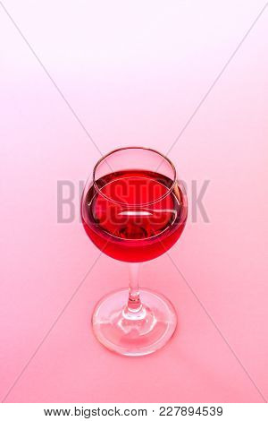 A Glass Of Red Wine On Pink Background