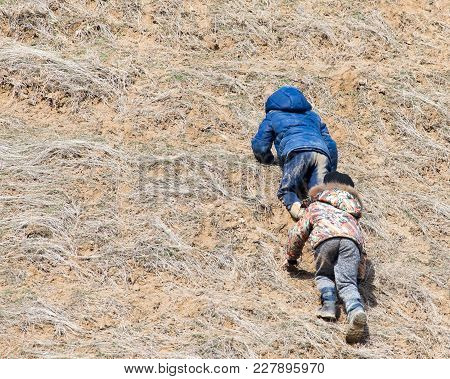 Two Boys Are Going Uphill . In The Park In Nature