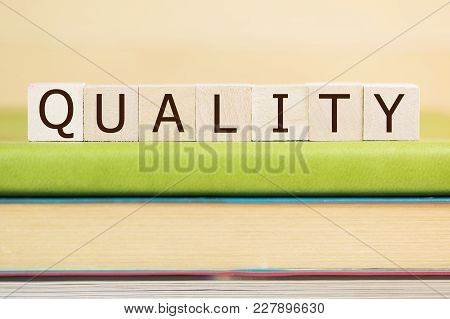 Quality Word Built With Letter Cubes On Green Book