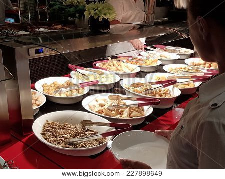 The Girl Chooses Food In An Asian Restaurant Pay-what-you-want  Chooses Among The Numerous Egozotic