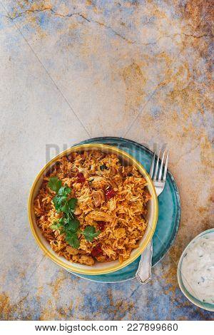 Chicken And Vegetable Biryani With Cucumber Raita Side Dish. Top View, Blank Space, Rustic Backgroun