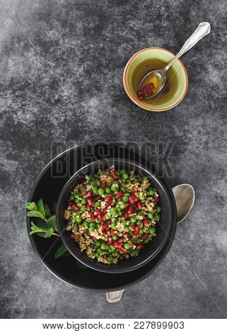 Lebanese Bulgur Salad With Green Pea , Pomegranate Seed And Dressing. Top View, Blank Space, Dark To