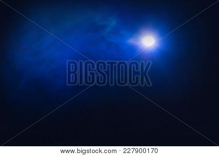 Lamp In The Dark With Smoke. On A Dark Blue Background With A Haze, A Bright Point Of Light Shines B