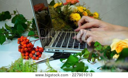 Close-up Of Hands Of Good-looking Female Florist Who Prints Text On Laptop Keyboard And Responds To