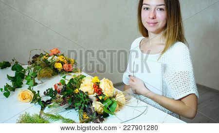 Good-looking Young Woman Florist Of European Appearance Beautifully Smiling And Posing, Holding Note