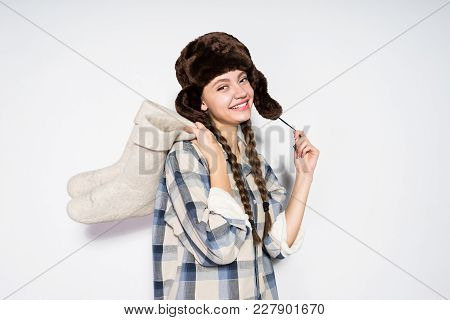 A Smiling Young Girl From Russia In A Warm Fur Hat Holds Gray Felt Boots In Her Hands, Her Hair Is B