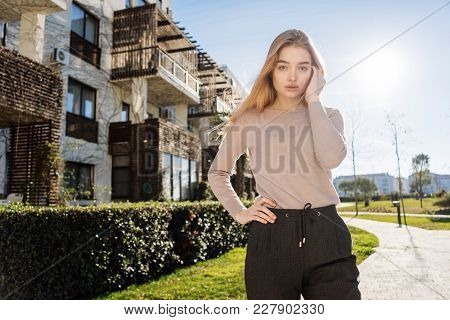 Beautiful Young Blonde Girl Walking Along The Street In The Sun