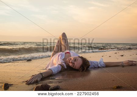 Girl Rests And Has Fun In Sea Wave At Sunset In The Evening