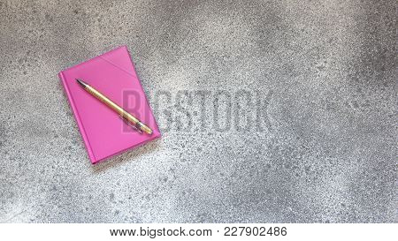 Pink Diary On A Gray Concrete Background And Golden Elegant Ballpoint Pen. Office Desktop With Pen A