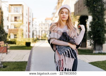 Beautiful Young Blond Girl In A Hat Walking Through The Streets Of The City, Enjoying The Spring Wea