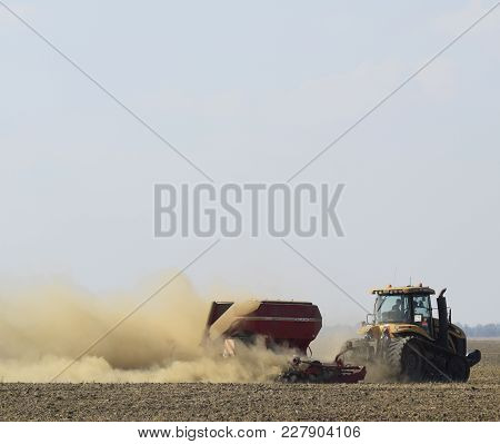 Russia, Temryuk - 19 July 2015: Tractor Rides On The Field And Makes The Fertilizer Into The Soil. C
