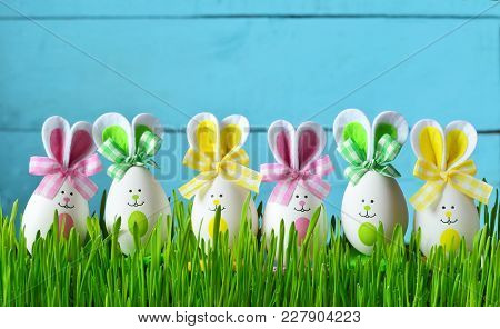 Easter Funny Bunny On Green Grass And Easter Eggs. Easter Background