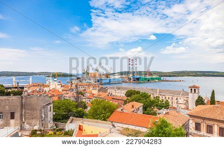 Aerial View Of Roof Tops With Shipyard At The Background In Old Town Pula City Of Croatia.