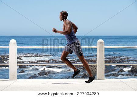 Full Length Healthy Young African American Man Running By Sea
